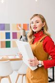 Attractive Magazine Editor With Folder In Modern Office With Colleague And Color Palette On Wall Beh poster