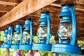 Perspective View Of Storm Lanterns Hanged On Wooden Counterpoise