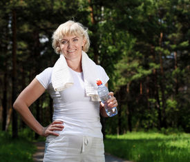 stock photo of drinking water  - An elderly woman after exercising in the forest holding a bottle of water - JPG