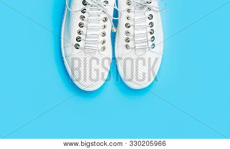 poster of Sneakers Isolated On Blue Background, Fashion. White Shoes. Pair Of White Shoes On Blue Background.