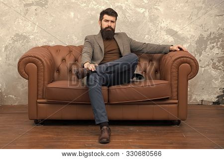poster of Rent Apartment. Bearded Man With Confident Face Sit Leather Couch. Loft Interior Apartment. Business