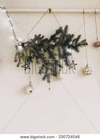 poster of Stylish Christmas Tree Branch With Lights And Glass Ornaments Hanging On White Wall. Modern Eco Deco