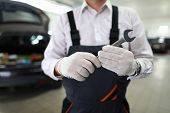 Focus On Automechanic Male Hand In White Gloves Holding And Showing Utility For Fixing Car At Camera poster