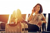 Air Travel Concept With Young Casual Girl Sitting With Hand Luggage Suitcase. Airport Woman Talking  poster