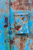 A Blue Rusty Door With A Rusty Postbox poster