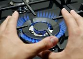 Hands Of A Man Close-up Near A Gas Stove. A Man Warms His Hands By The Stove Due To Poor Heating At poster