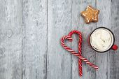 Red Mag Of Drink With Candy Cane And Christmas Gigerbread On Wooden Background. Copy Space poster