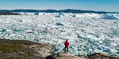 Travel in arctic landscape nature with icebergs - Greenland tourist man explorer - tourist person lo poster