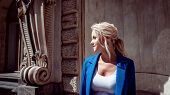 Walk Through The Historic Center. Beautiful Girl, Blonde With A Ponytail And Curls In A Blue Pantsui poster