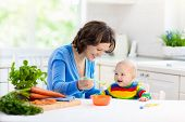 Mother Feeding Baby First Solid Food poster