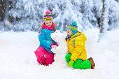 Kids Making Winter Snowman. Children Play In Snow. poster