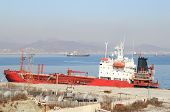 picture of raid  - Red tanker standing at old mooring against ships on raid - JPG