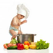 Little boy with ladle, casserole, and vegetables