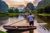 Fisherman On Boat In Trang An, Near Ninh Binh, Vietnam poster