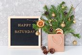 Happy Saturday Text On Black Letter Board And Festive Bouquet Of Fir Branches With Christmas Decor I poster
