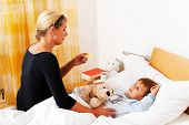 a mother and sick child in bed. flu. childhood diseases.