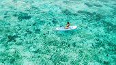 Woman Sitting On Sup Board And Enjoying Turquoise Transparent Water And Coral Reef. Tropical Travel, poster