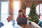 Beautiful woman sitting at the table working with laptop at home around christmas tree tired rubbing poster