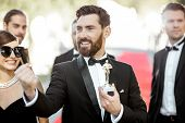 Portrait Of An Elegant Man As A Well-known Movie Actor Holding Famous Academy Award During Awards Ce poster