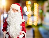 Middle age handsome man wearing Santa Claus costume and beard standing afraid and shocked with surpr poster
