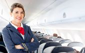 stock photo of cabin crew  - Beautiful air hostess in an airplane smiling - JPG