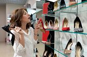 Interested Woman Holding Black Heeled Shoe And Red Defocused Heeled Shoe In Shop. Photo With Depth O poster