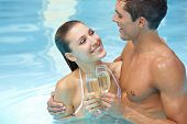 Happy attractive couple drinking sparkling wine in swimming pool