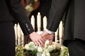 Religion, death and dolor  - couple at funeral holding hands consoling each other in view of the los