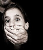 Girl being abused and silenced by a partially hidden adult man who has a hand covering her mouth