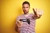 Young handsome man playing video games using joystick game pad over yellow background pointing with  poster