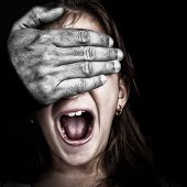 Close up of a girl being abused  by an adult  with a desaturated hairy hand covering her eyes while