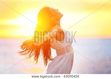 Enjoyment - free happy woman enjoying sunset. Beautiful woman in white dress embracing the golden su poster
