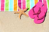 stock photo of thong  - Tropical beach vacation holiday and travel concept with a colourful striped beach towel and vibrant pink sandal flip flip thongs on pristine sand with a starfish at an idyllic coastal beach resort - JPG