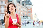 Tourist woman eating ice cream in Quebec City in front of chateau frontenac in Quebec City, Quebec,