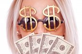 Close up shot of Dollar sign sunglasses and fan of hundred Dollar bills - making money concept