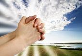 stock photo of praying hands  - a pair of hands in a praying position set against a beautiful prairie lake landscape - JPG