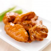 plate of buffalo wings with celery closeup
