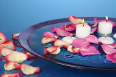 Rose petals and candles in water in vase on blue background close-up