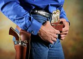 stock photo of gunfights  - waist section of a western era cowboy with gun and holster - JPG