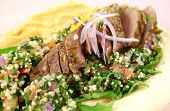 stock photo of tabouleh  - Sliced Middle Eastern lamb fillet with hummus and tabouleh - JPG
