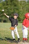 Boy Throwing Baseball From First Base