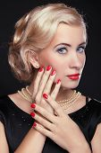 Blond Woman With Make Up And Red Manicured Nails Over Black, Studio Photo