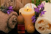 spa concept with cotton towels, massage oil, loofah, aromatic lavender and candles