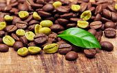 Green and black coffee beans on wooden background.