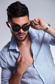 young casual man pulling down his sunglasses while opening his shirt and looking into the camera. on
