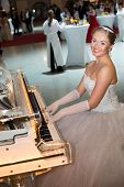 MOSCOW - MAY 25: Beautiful smiling girl in a wedding dress playing the piano at 11th Viennese Ball i