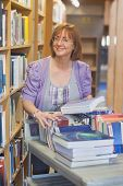 picture of librarian  - Female mature librarian returning books in library smiling at camera - JPG