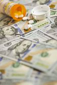 Medicine Pills Scattered on Newly Designed U.S. One Hundred Dollar Bills.