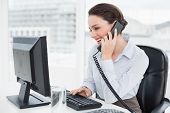 Smiling elegant businesswoman using landline phone and computer in a bright office