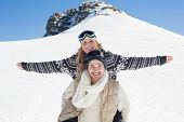 Young man piggybacking cheerful woman against snow covered hill and clear blue sky